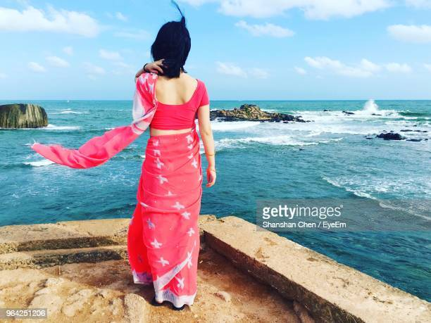 rear view of woman in sari standing at beach against sky - sari stock pictures, royalty-free photos & images