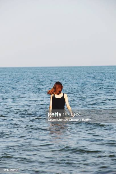 rear view of woman in sea against clear sky - waist deep in water stock pictures, royalty-free photos & images