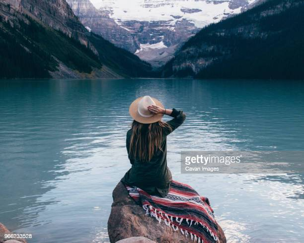 rear view of woman in sun hat sitting on rock and looking at view - lake louise stock pictures, royalty-free photos & images
