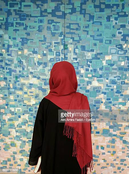 Rear View Of Woman In Traditional Clothing Against Blue Patterned Wall