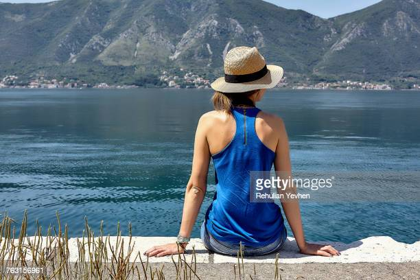 Rear view of woman in trilby sitting on waterfront looking out at the Bay of Kotor, Montenegro