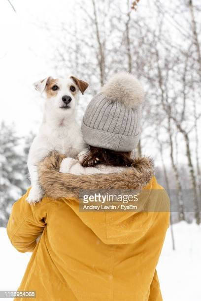 rear view of woman in warm clothing carrying dog in snow covered forest - jacke stock-fotos und bilder