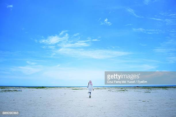 rear view of woman islamic walking on beach - muslim woman beach stock photos and pictures
