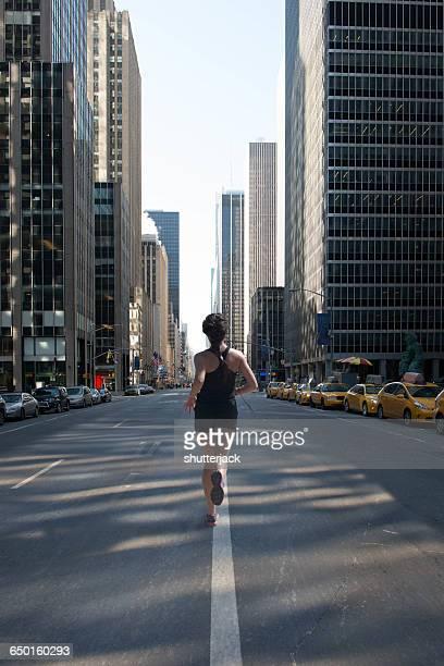 rear view of woman jogging down avenue of americas (6th avenue), manhattan, new york, america, usa - ponto de fuga imagens e fotografias de stock