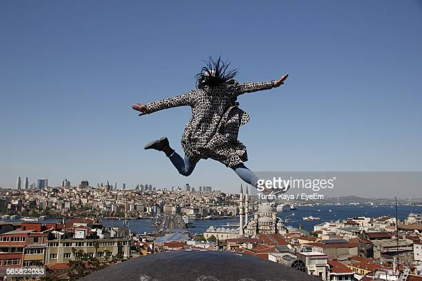 Rear View Of Woman Jumping On Rock Against Clear Blue Sky
