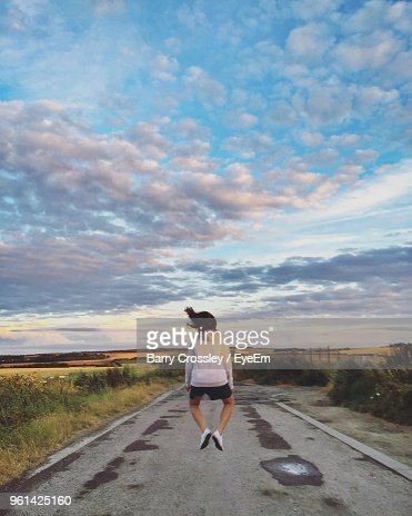 Rear View Of Woman Jumping Over Road Against Sky