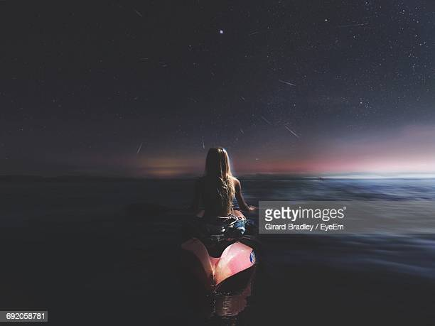Rear View Of Woman Kayaking At Sea Against Star Field