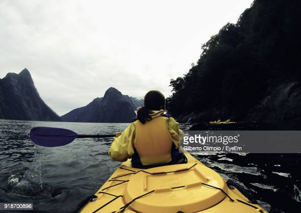 rear view of woman kayaking over lake against sky - southland new zealand stock pictures, royalty-free photos & images