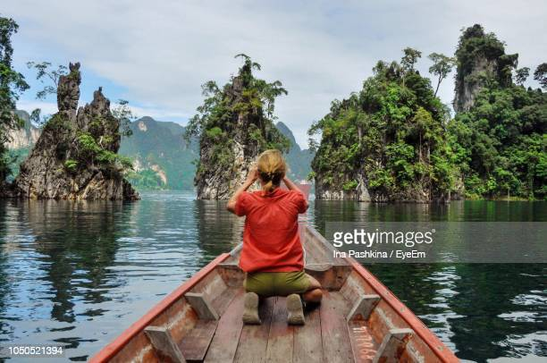 rear view of woman kneeling on boat while looking at rock formations in lake - destination de voyage photos et images de collection
