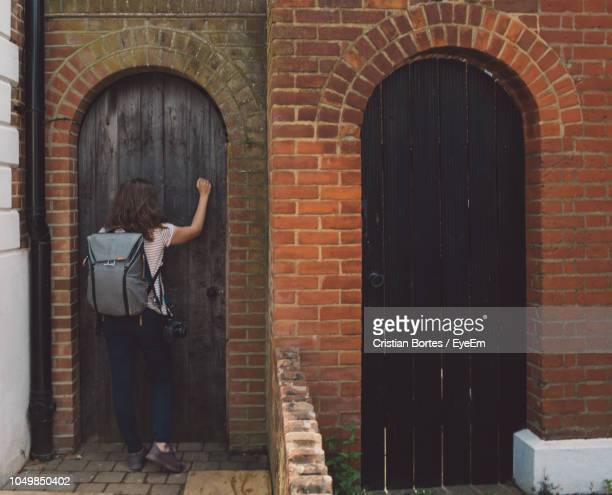 Rear View Of Woman Knocking Door