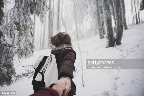 Rear View Of Woman Leading Man In Snow Covered Forest