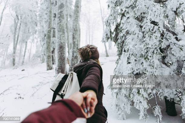 Rear View Of Woman Leading Man In The Snow