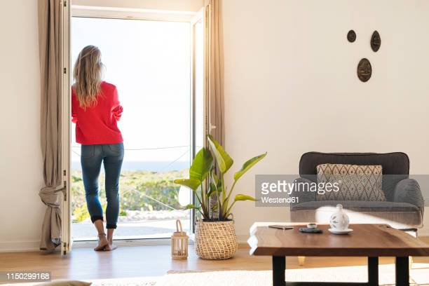 rear view of woman leaning at open window at home looking at the sea - holiday villa stock pictures, royalty-free photos & images
