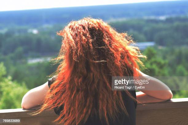 Rear View Of Woman Leaning On Railing Against Green Landscape