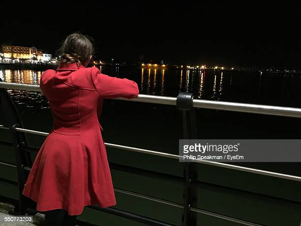 rear view of woman leaning on railing while looking at river during night - portsmouth england stock pictures, royalty-free photos & images