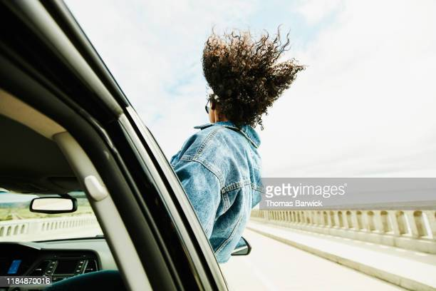 rear view of woman leaning out of car window with hair blowing in wind - windzerzaustes haar stock-fotos und bilder