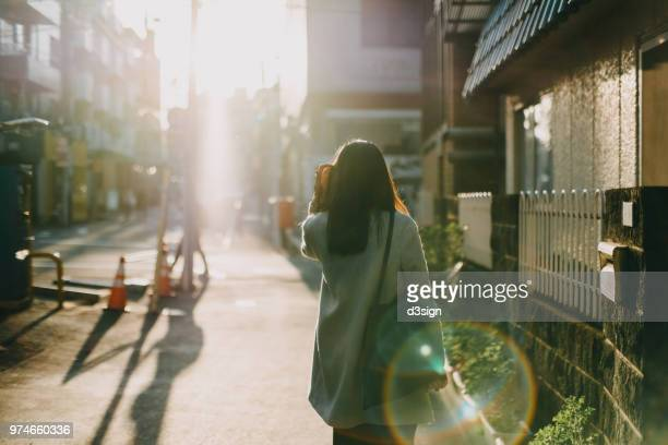 rear view of woman leaving home to work in the early morning against warm sunlight - ochtend stockfoto's en -beelden