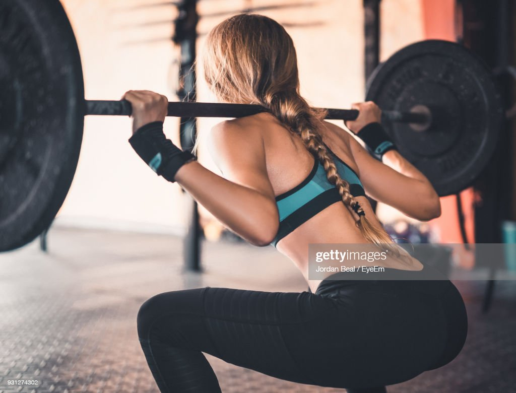 Rear View Of Woman Lifting Weights In Gym : Stock Photo