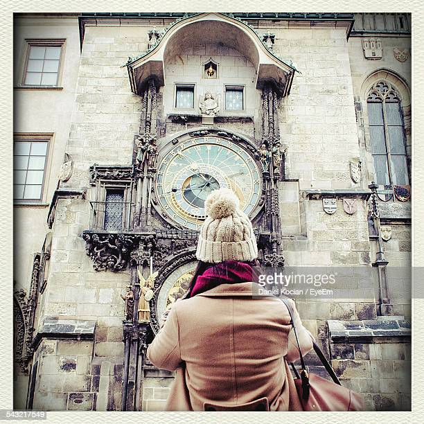 rear view of woman looking at astronomical clock on historic building - astronomical clock prague stock pictures, royalty-free photos & images