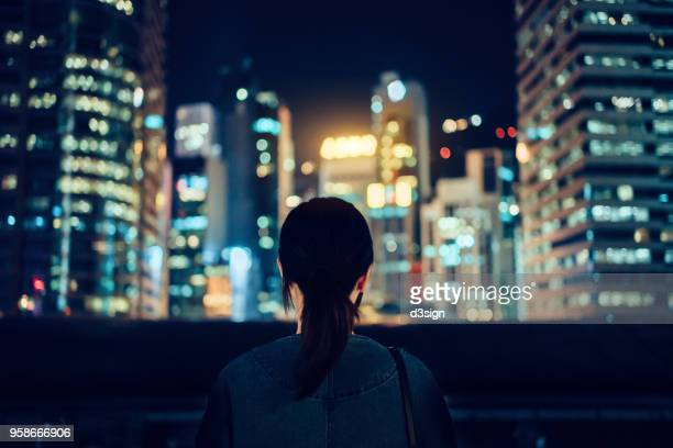 Rear view of woman looking at city at night