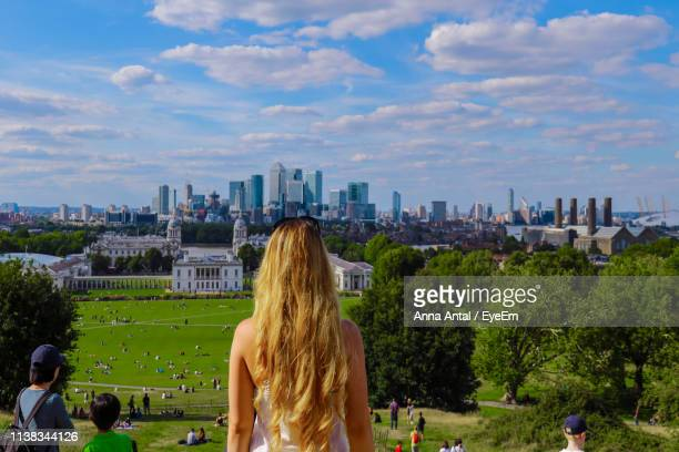 rear view of woman looking at city buildings from park against cloudy sky - london docklands stock pictures, royalty-free photos & images