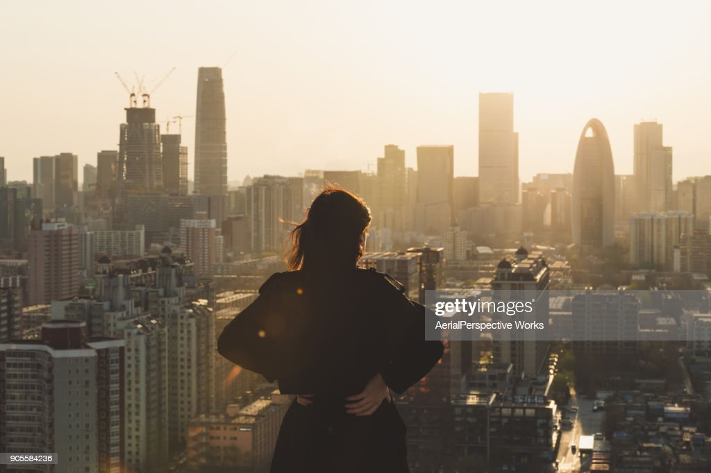 Rear view of Woman looking at city in Sunlight : Stock Photo