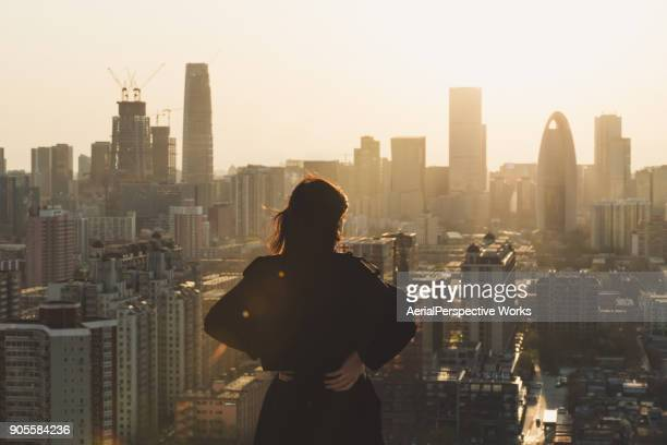rear view of woman looking at city in sunlight - paesaggio urbano foto e immagini stock