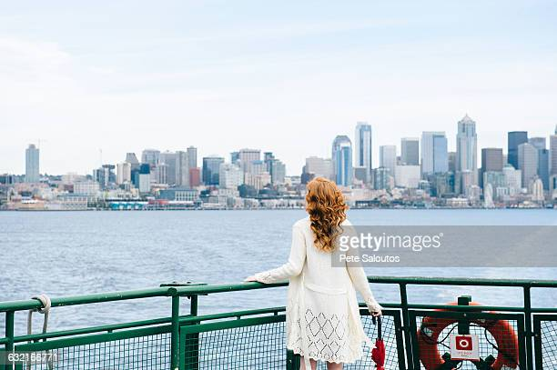 rear view of woman looking at city skyline from passenger ferry on puget sound, seattle, usa - puget sound stock pictures, royalty-free photos & images