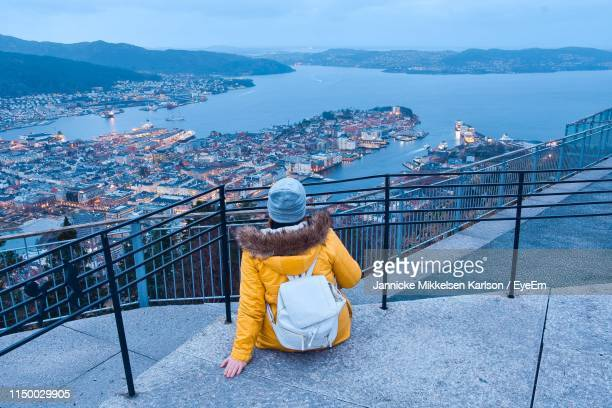rear view of woman looking at cityscape by sea and mountain during sunset - bergen norway stock pictures, royalty-free photos & images