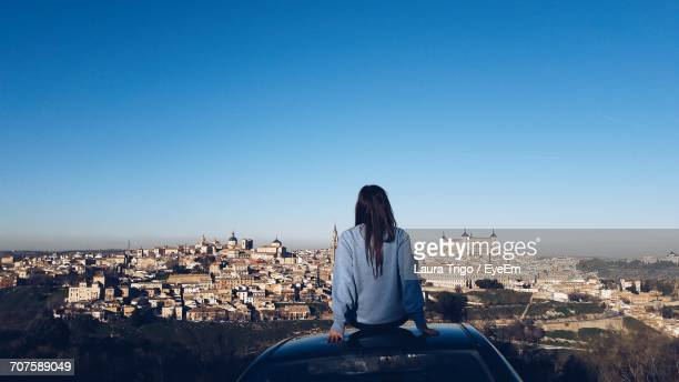 rear view of woman looking at cityscape while sitting on car roof against clear blue sky - la mancha fotografías e imágenes de stock