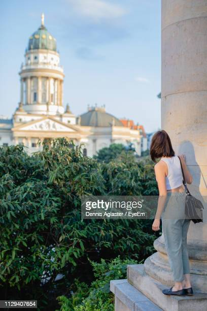 rear view of woman looking at concert hall while standing on column in city - konzerthaus berlin stock pictures, royalty-free photos & images
