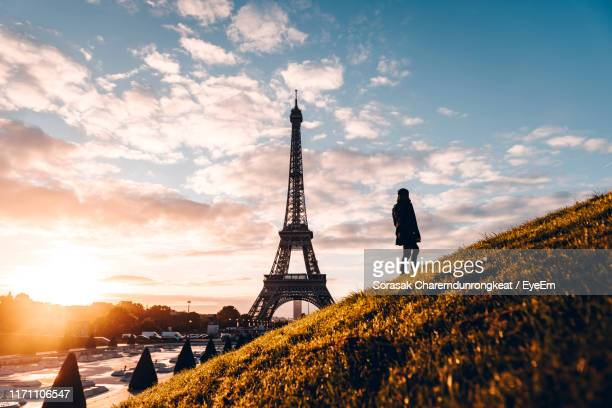 rear view of woman looking at eiffel tower while standing on hill - paris france fotografías e imágenes de stock