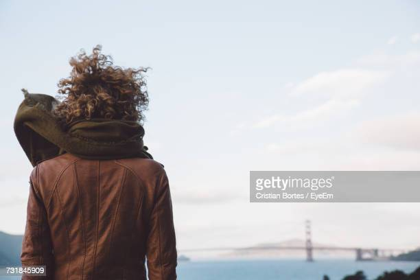Rear View Of Woman Looking At Golden Gate Bridge Against Sky