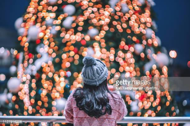 rear view of woman looking at illuminated christmas lights - christmas scenes stock photos and pictures