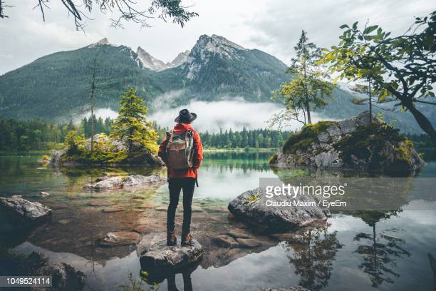 rear view of woman looking at lake against mountains - buitensport stockfoto's en -beelden
