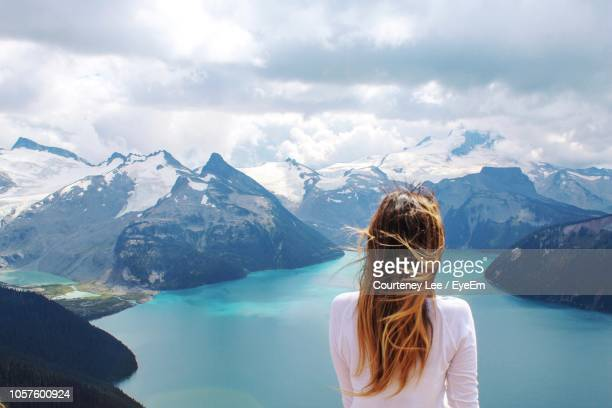 rear view of woman looking at lake by snowcapped mountains against cloudy sky - chica morena de espaldas fotografías e imágenes de stock