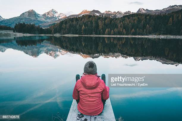 rear view of woman looking at lake during winter - aussicht genießen stock-fotos und bilder