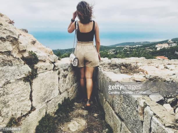 rear view of woman looking at landscape against sky - file:the_wyoming,_orlando,_fl.jpg stock pictures, royalty-free photos & images