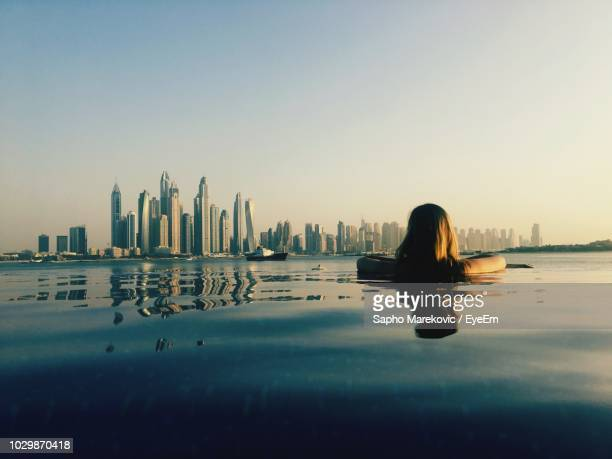 rear view of woman looking at modern building while swimming in infinity pool against clear sky during sunset - infinity pool foto e immagini stock