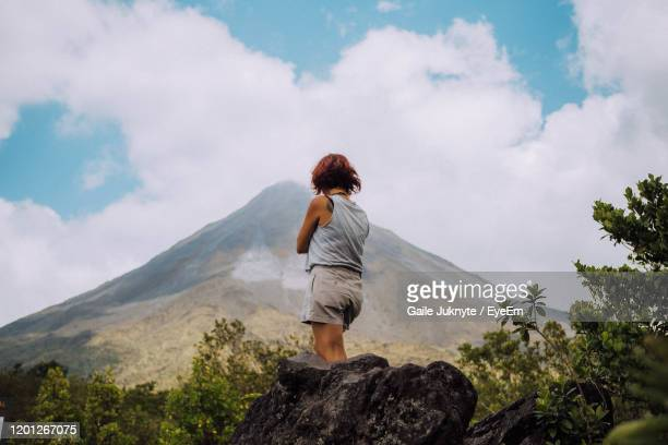 rear view of woman looking at mountain against sky - costa rica stock-fotos und bilder