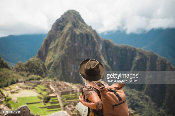 rear view of woman looking at mountains against sky - peru stock-fotos und bilder