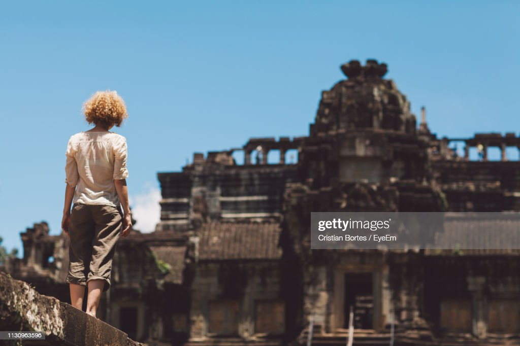 Rear View Of Woman Looking At Old Historical Building During Sunny Day : Stock Photo