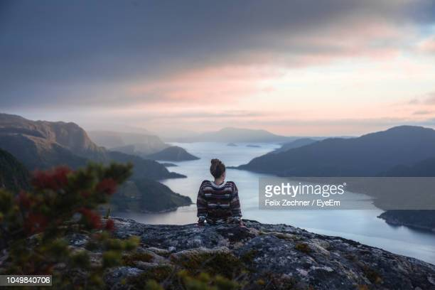 rear view of woman looking at river amidst mountains against sky during sunset - norwegen stock-fotos und bilder