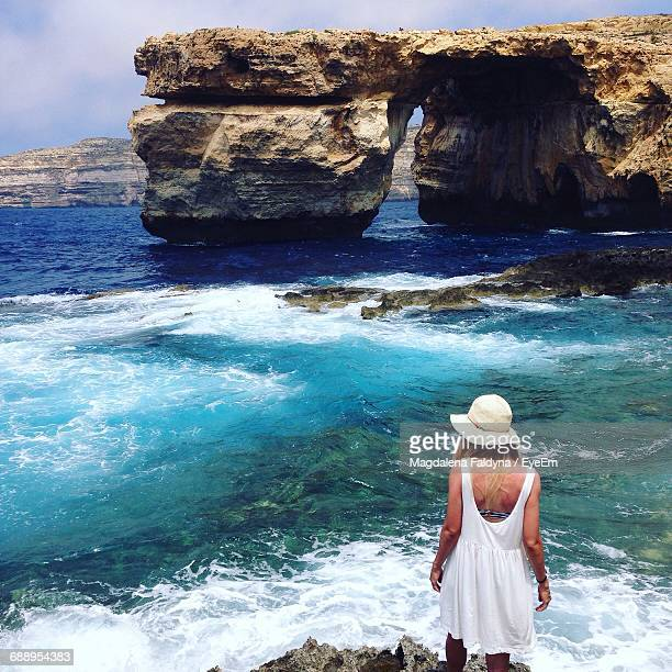 rear view of woman looking at rock formation in sea - malta fotografías e imágenes de stock