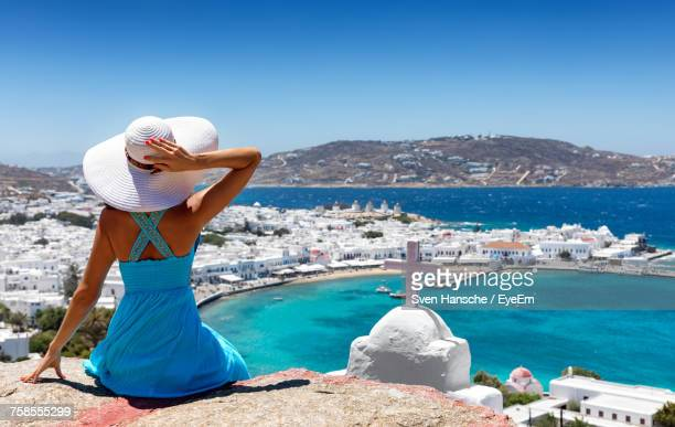 Rear View Of Woman Looking At Sea Against Clear Sky During Sunny Day