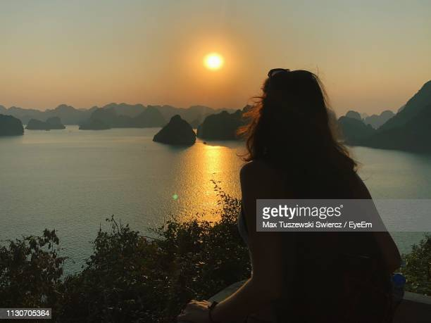 rear view of woman looking at sea against sky during sunset - pretty vietnamese women stock pictures, royalty-free photos & images