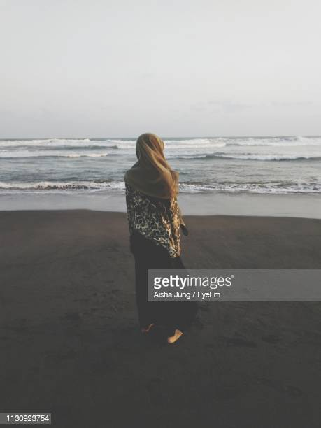 rear view of woman looking at sea against sky - muslim woman beach stock photos and pictures