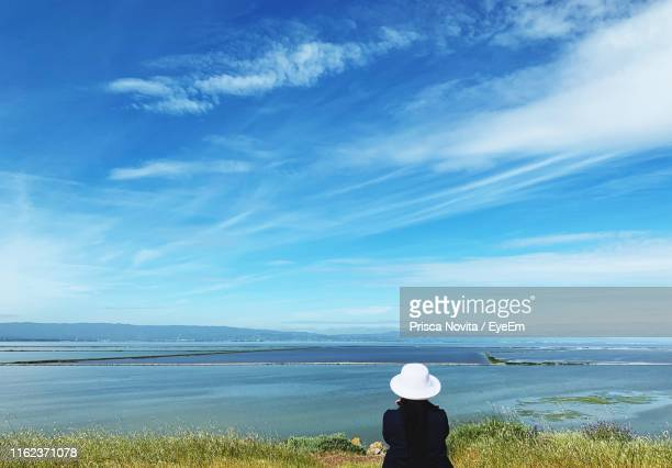 rear view of woman looking at sea against sky - fremont california stock pictures, royalty-free photos & images
