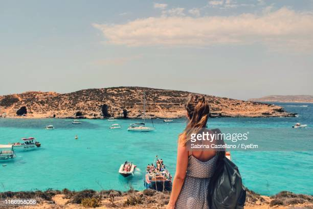 rear view of woman looking at sea against sky - malta stock pictures, royalty-free photos & images