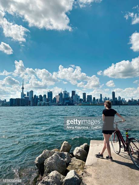 rear view of woman looking at sea and buildings against sky - canada stock pictures, royalty-free photos & images